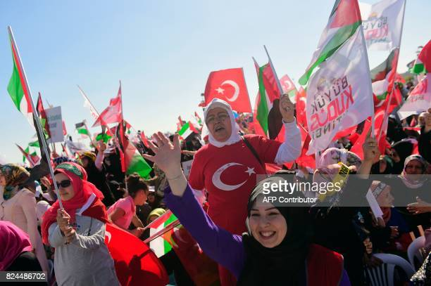 Protesters wave Turkish and Palestinian flags as they shout slogans during a demonstration in Istanbul on July 30 to protest against measures taken...
