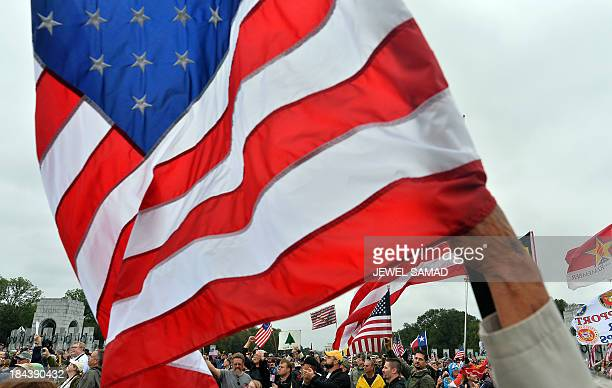 Protesters wave US flags during a demonstration at the World War II memorial on October 13 2013 in Washington DC The demostrators are demanding an...