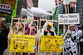 Protesters wear animal costumes and hold fake fences with a sign reading 'that's how I am fenced in me poor pig' while taking part in a demonstration...