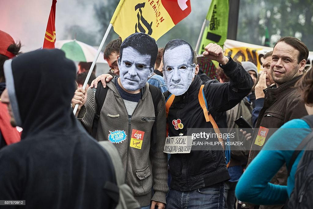 Protesters wearing a mask depicting the French prime minister and the head of Medef the French employers' federation take part in a demonstration of...