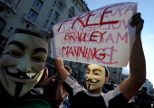 Protesters wearing anonymous masks hold up a sign demanding the release of Bradley Manning the US soldier accused of passing restricted material to...