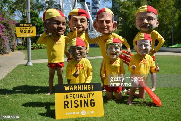 Protesters wearing fiberglass heads depicting world leaders and dressed in lifesaver uniforms to highlight the need to halve global inequality pose...