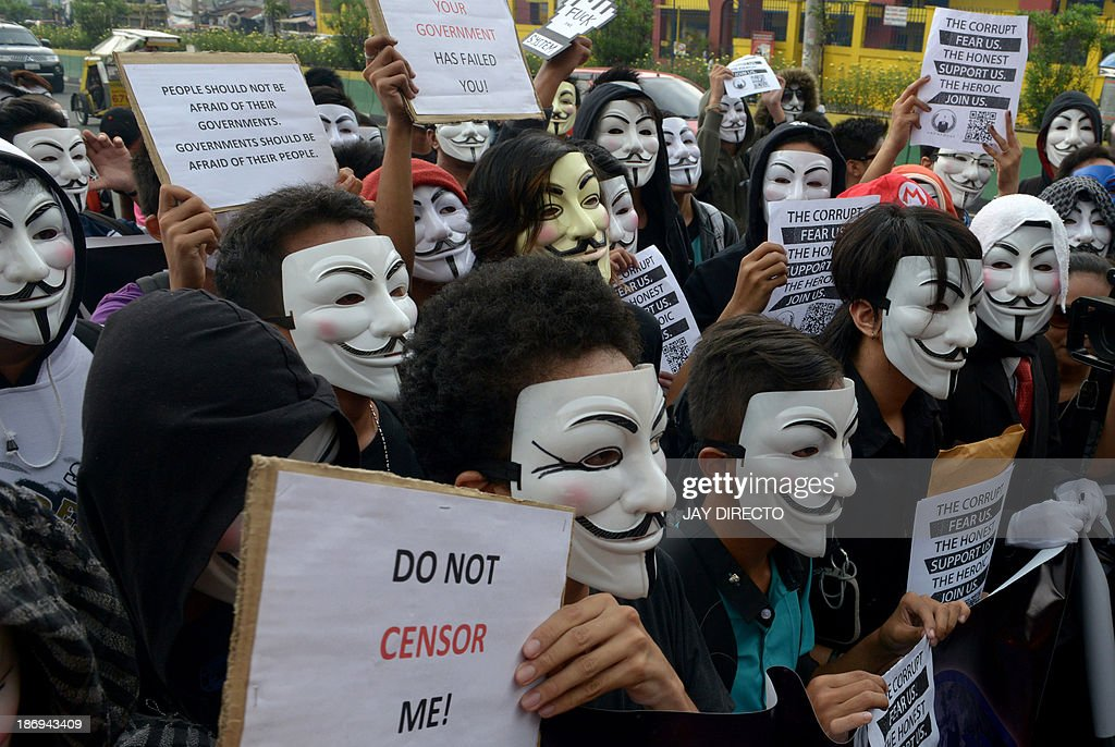 Protesters wearing Guy Fawkes masks display placards during a rally outside the House of Representatives in suburban Quezon city, north of Manila on November 5, 2013. Some 100 masked members of the hacking group Anonymous Philippines marched on parliament on November 5, denouncing corruption and pledging more cyber attacks, a week after 30 government websites were paralysed. AFP PHOTO / Jay DIRECTO