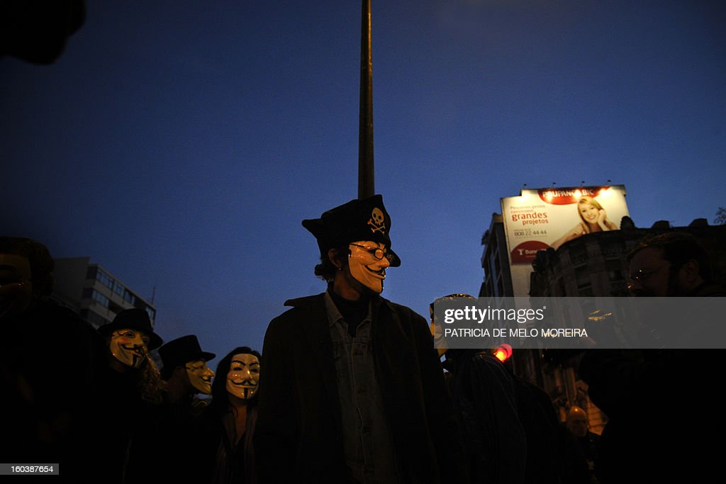Protesters wearing Guy Fawkes masks gather outside the International Monetary Fund (IMF) headquarters in Lisbon on January 30, 2013, to protest against government's austerity measures imposed by the European Union and the IMF.