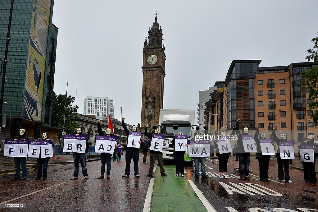 Protesters wearing Guy Fawkes masks hold Unison placards spelling out the message 'Free Bradley Manning', referring to the US soldier Bradley Manning who is suspected of passing sensitive US government material to whistleblowing website WikiLeaks, as they join with trade unionists and others for a planned rally in Belfast, Northern Ireland, on June 15, 2013. Many protetsers carried anti-G8 placards during the event which culminated with a Loyalist flag protest ahead of the G8 talks that start on June 17 in Northern Ireland.