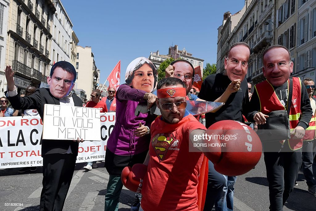 TOPSHOT Protesters wearing masks depicting French Prime Minister French Labour Minister and French President pose during a demonstration against the...