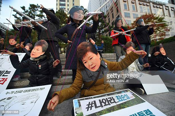 Protesters wearing masks of South Korean President Park GeunHye and her confidante Choi SoonSil perform before a candlelit rally in central Seoul on...