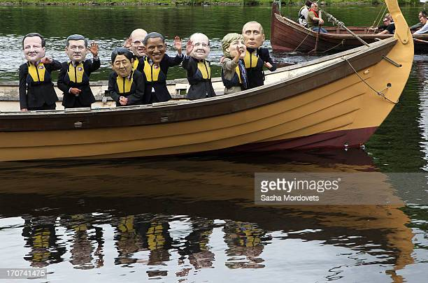 Protesters wearing masks of the G8 Leaders stand in a boat on Lough Erne during the first day of the G8 Summit on June 17 2013 in Enniskillen...