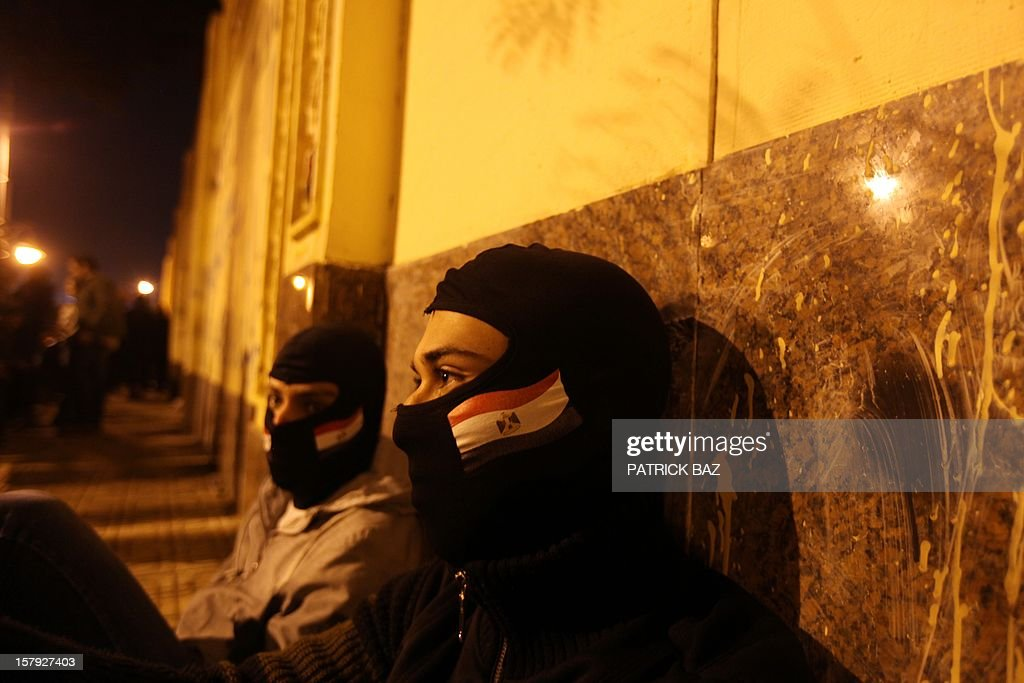 Protesters wearing ski masks sit outside the Egyptian presidential palace as thousands of protesters against Egyptian president Mohammed Morsi gather in front of the palace on December 7, 2012 in Cairo. Thousands of protesters broke through a barbed-wire perimeter protecting Morsi's palace, as his vice-president hinted at a possible compromise aimed at calming the seething crisis dividing Egypt.