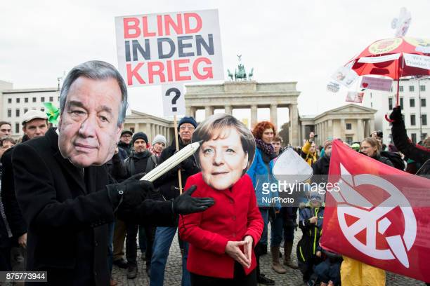Protesters wearing the masks of UN Secretary General Antonio Guterres and German Chancellor Angela Merkel attend a demonstration organized from...
