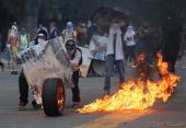 Protesters wheel a burning tire towards Venezuelan national policemen during an antigovernment protest on March 6 2014 in Caracas Venezuela...