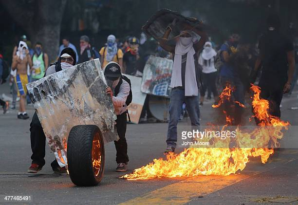 Protesters wheel a burning tire towards Venezuelan national policemen during an antigovernment protest on March 6 2014 in Caracas Venezuela...