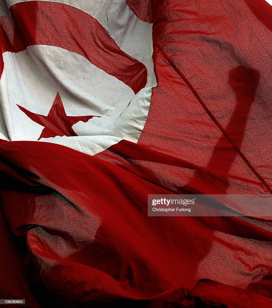 Protesters who marched from the rural areas of Tunisia campaign with the national flag outside the prime minister's office for the remnants of the...