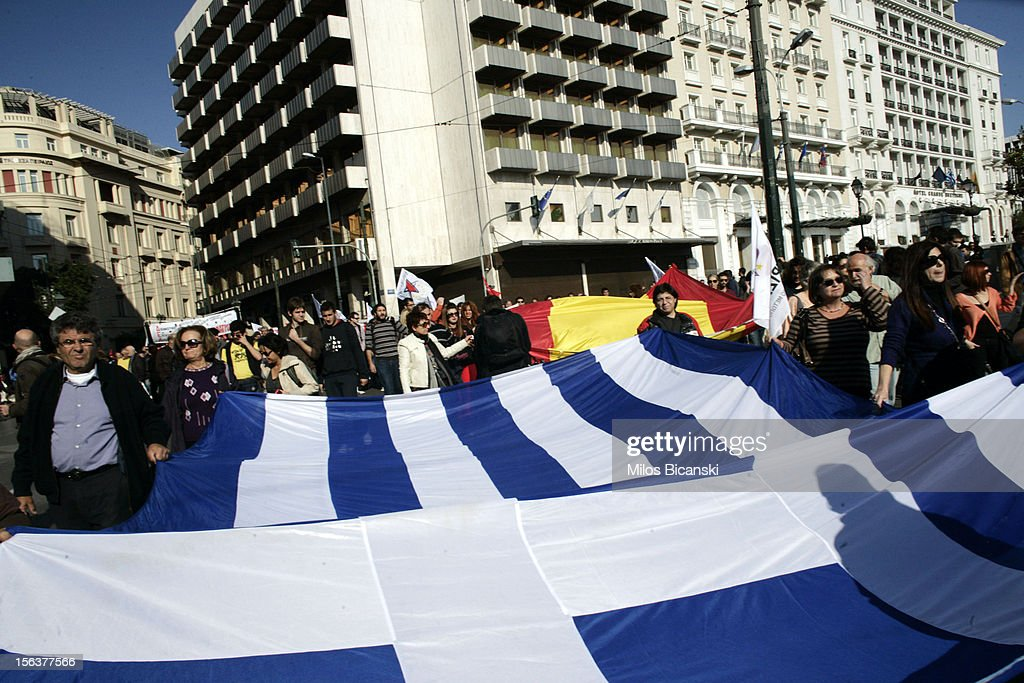 A protesters with a Greek flag and Spain flag (back) marches during an anti-austerity protest on November 14, 2012 in Athens, Greece. Unions in Spain, Portugal and Greece went on strike in what has become the first broad-based anti-austerity action to protest government plans amid a wide economic scope across Europe.