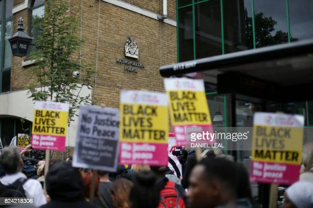 Protesters with placards from the Black Lives Matter campaign group are seen at a vigil over the death of Rashan Charles whose death after being...