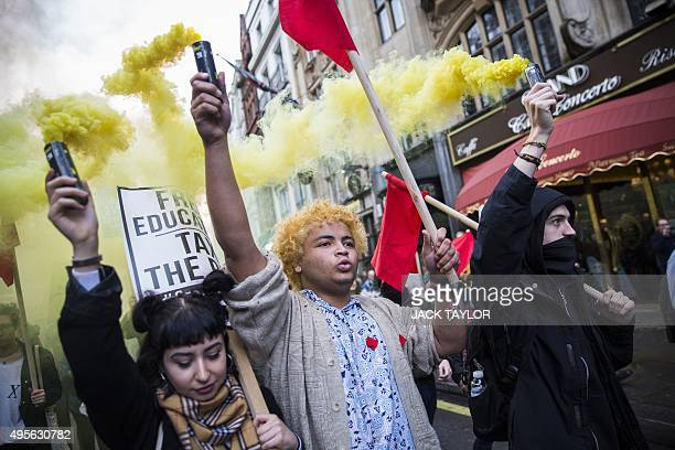 Protesters with smoke canisters walk during the annual demonstration against student fees in central London on November 4 2015 Students marched...