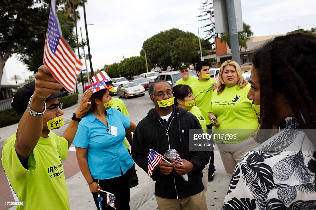 Protesters with the Organization United for Respect at Walmart (OUR Walmart) wear tape over their mouths during a demonstration outside a Wal-Mart Stores Inc. location in Los Angeles, California, U.S., on Tuesday, July 2, 2013. Southern California community supporters joined Wal-Mart Stores Inc. workers to protest against alleged illegal violations of employees labor rights and freedom of speech. Photographer: Patrick T. Fallon/Bloomberg via Getty Images