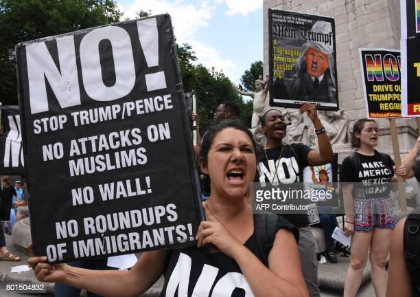 TOPSHOT Protesters with 'Today Refuse Fascism' hoist signs at Columbus Circle in New York City June 26 2017 prior to a march to Trump Tower to...