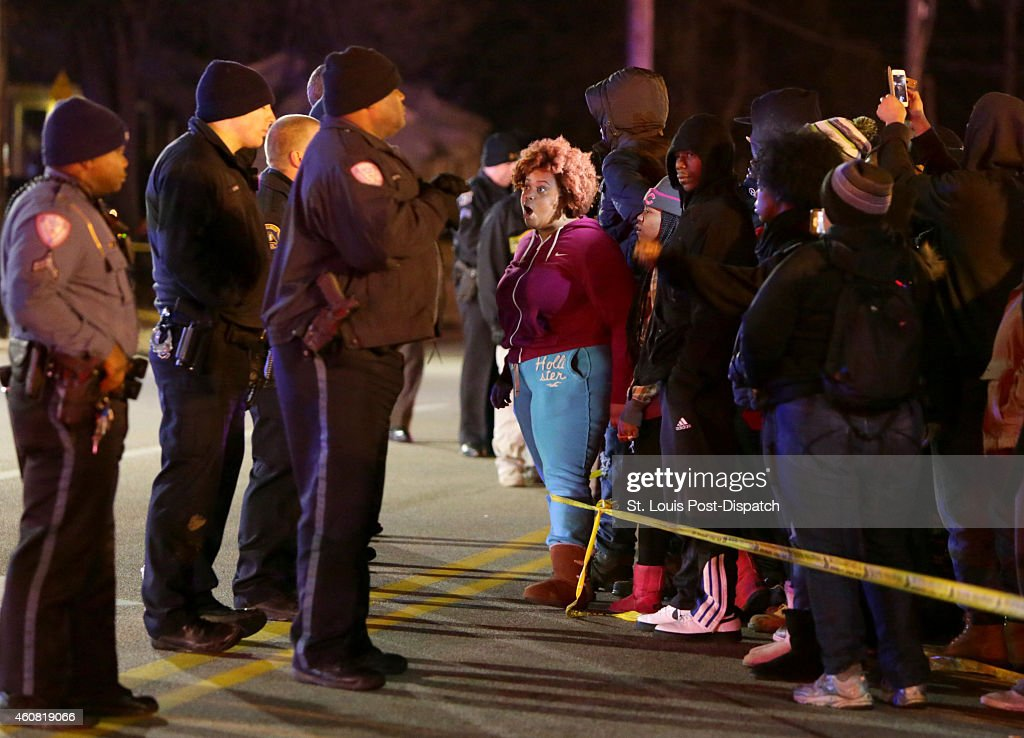 Protesters yell at police protecting the perimeter of a scene on Wednesday Dec 24 2014 where teenager was fatally shot by a police officer about 90...