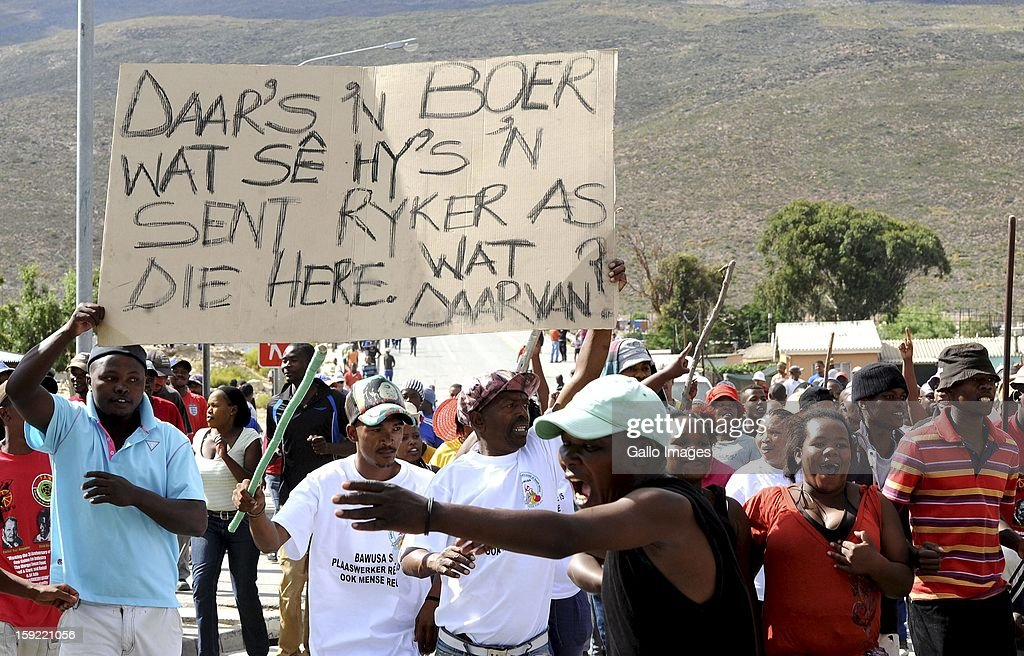 Protesting farm workers at De Doorns on January 9, 2013, in Cape Town, South Africa. The farm workers shut down the N1 by lighting tires on fire and placing large rocks on the road and demanded wages of R150 per day.