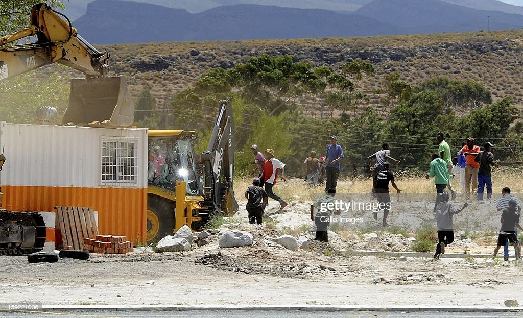 Protesting farm workers at the N1 highway De Doorns protest on January 9, 2013, in Cape Town, South Africa. The farm workers shut down the N1 by lighting tires on fire and placing large rocks on the road as they demanded wages of R150 per day.