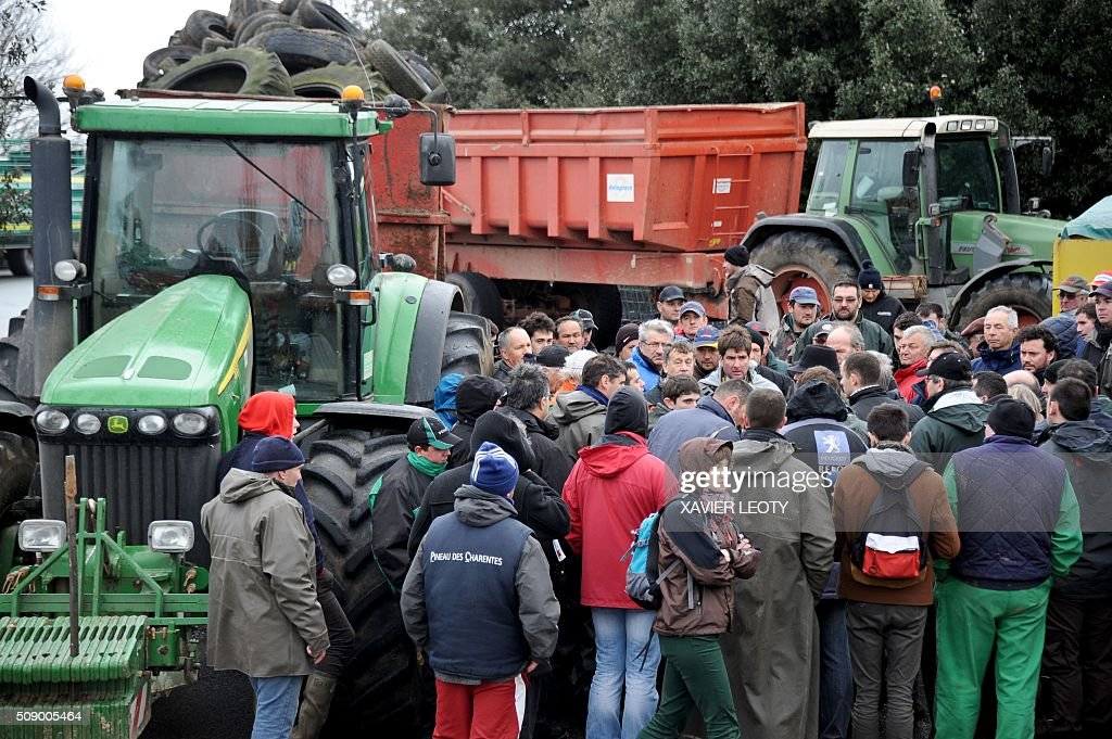 Protesters stand near tractors as they block a road near Saintes, western France, on February 8, 2016, during a demonstration against the purchase price of their products by supermarkets. Over 100 tractors were used by mostly pig and dairy farmers to block strategic points giving access to the city, disrupting traffic and closing an interchange of the A10 motorway. / AFP / XAVIER LEOTY