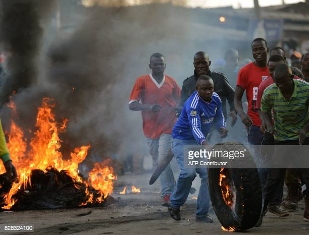 Protesting residents push a flaming tyre towards a burning barricade on a road in Kibera Slum in Nairobi on August 9 as they take part in protests in...