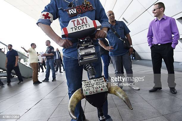 A protesting taxi driver rides a toy scooter onto which he attached a taxi luminous signing reading 'Toy Scooter Taxi' a taxi meter and horns reading...
