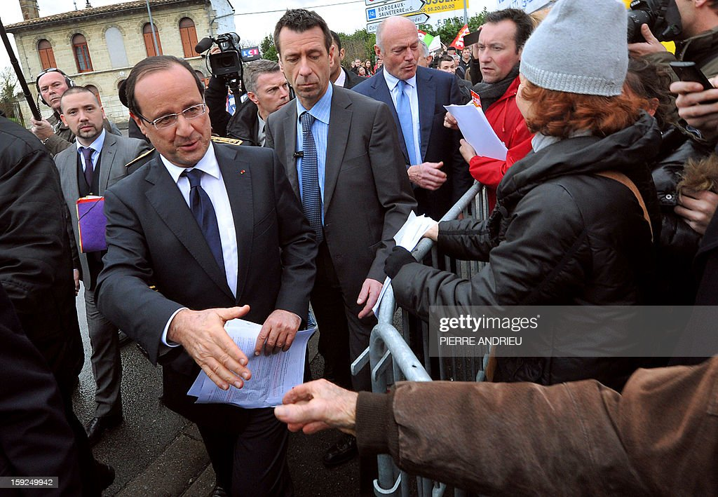 Protesting workers from local companies which risk having to close down give fliers to French President Francois Hollande (3rd L) in Latresne, southwestern France, on January 10, 2013, ahead of a visit of the Aerocampus site. Hollande was in the region for a visit dedicated to future investments and high-tech companies.