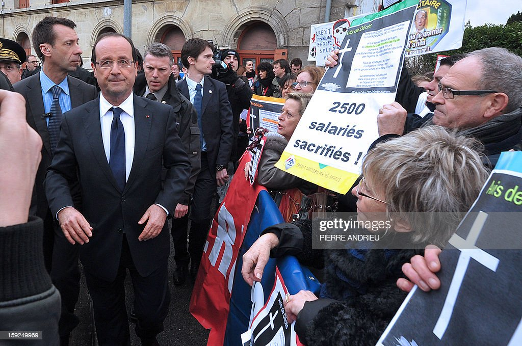 Protesting workers from local companies which risk having to close down show posters to French President Francois Hollande (3rd L) in Latresne, southwestern France, on January 10, 2013, ahead of his visit of the Aerocampus site. Hollande was in the region for a visit dedicated to future investments and high-tech companies. AFP PHOTO / POOL / PIERRE ANDRIEU