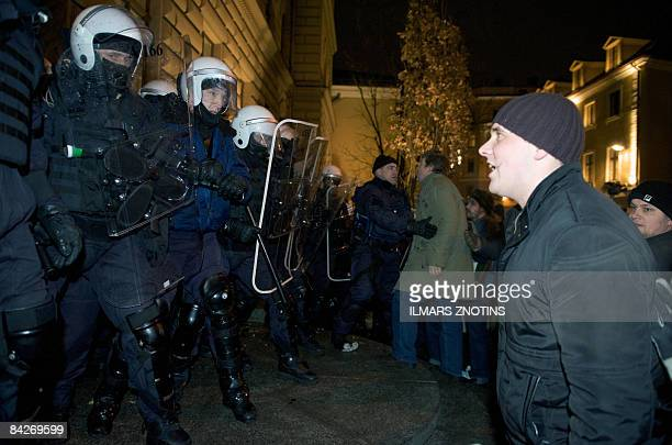 A protestor argues with helmeted antiriot policemen next to Saeima in Riga on January 13 2009 Thousands of people massed in the Latvian capital...