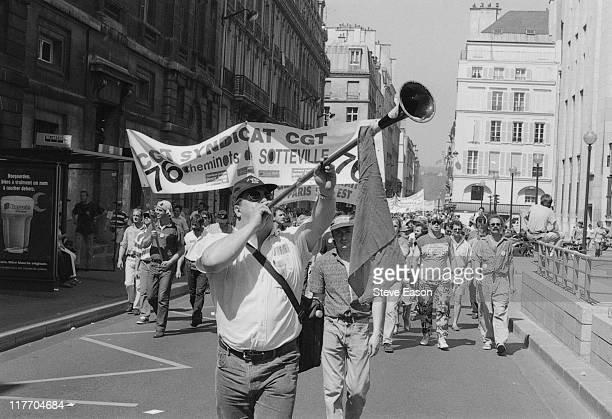 A protestor blowing a long coach horn as he leads French railway workers carrying a large banner in a demonstration by the French union federations...