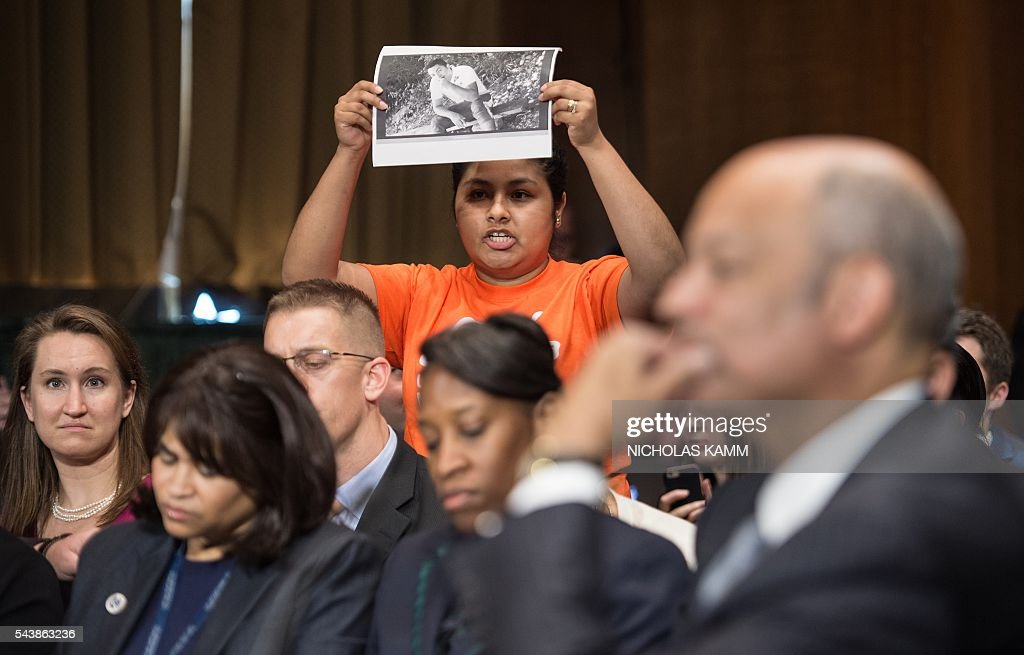 A protestor calls for the end of deportations of undocumented immigrants as Homeland Security Secretary Jeh Johnson (R) testifies at a Senate Judiciary Committee hearing on Oversight of the Department of Homeland Security on Capitol Hill in Washington, DC, on June 30, 2016. / AFP / NICHOLAS