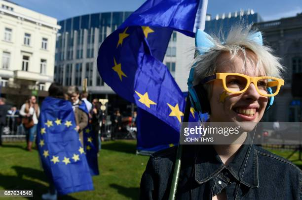 A protestor carries a European Union flag during a proEurope demonstration on March 25 2017 in front of at the EU Parliament in Brussels Rome hosts a...