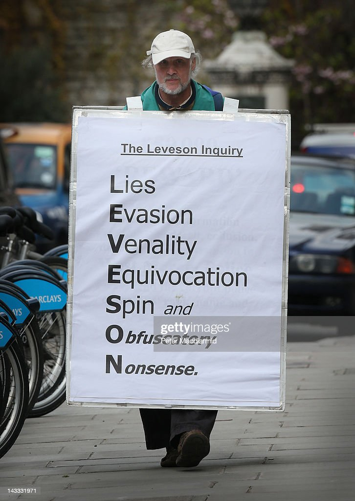 A protestor carries a placard outside the High Court as former News International chairman James Murdoch gives evidence to The Leveson Inquiry on...