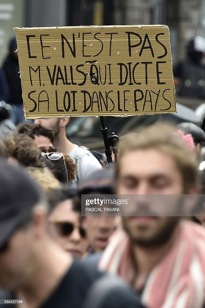 A protestor carries a sign reading 'It is not Mr. Valls that dictates the law in the country' during a demonstration against proposed government labour and employment law reforms on May 26, 2016 in Toulouse. Workers at nuclear power stations in France were set to go on strike May 26, joining a growing protest movement against controversial labour market reforms that has already severely disrupted fuel supplies. Unions have called for fresh rallies in cities across France on May 26, the latest bout of social unrest that started around three months ago and has frequently turned violent. PAVANI