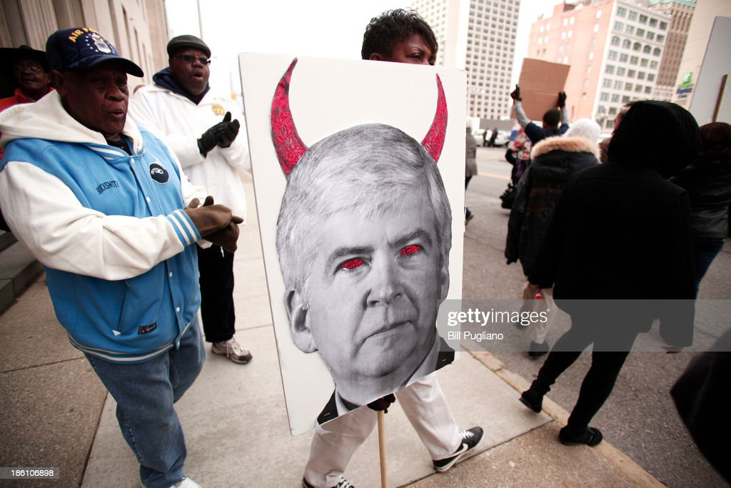 A protestor carries a sign that depicts Michigan Gov. Rick Snyder as a devil during a rally in front of the U.S. Courthouse in Detroit where Detroit's bankruptcy eligibility trial is taking place October 28, 2013 in Detroit, Michigan. Michigan Gov. Rick Snyder is expected to testify today at the trial. A federal judge will decide if the City of Detroit is eligible to be in bankruptcy court.
