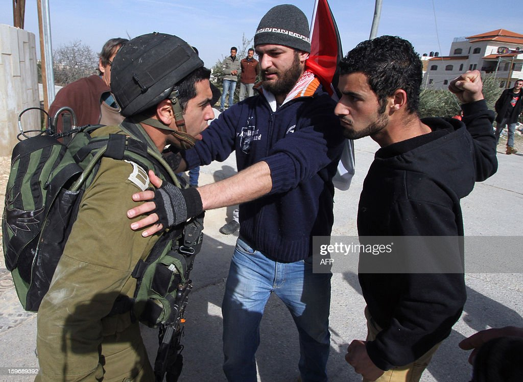 A protestor confronts an Israeli soldier during a weekly demonstration against Israel's controversial separation barrier in the West Bank village of Maasarah near Bethlehem on January 18, 2013. AFP PHOTO/MUSA AL SHAER