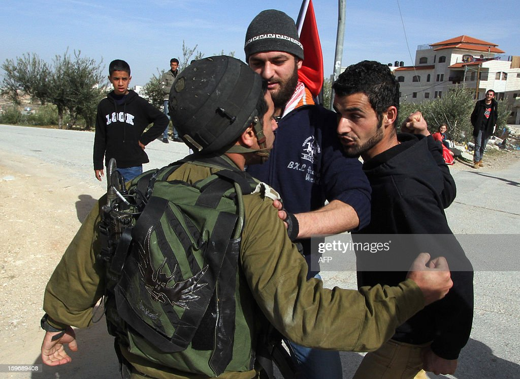 A protestor confronts an Israeli soldier during a weekly demonstration against Israel's controversial separation barrier in the West Bank Palestinian village of Maasarah near Bethlehem on January 18, 2013.