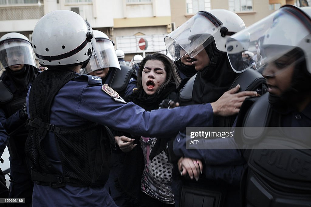 A protestor cries after being pepper sprayed as she is arrested by riot policemen during a demonstration called for by the February 14 Youth Coalition, an Internet group that regularly calls for protests in the Shiite-majority kingdom on January 18, 2013 in the capital Manama. Bahrain's government said the demonstration had not been authorised and warned security forces would prevent it from going ahead. AFP PHOTO/MOHAMMED ALSHAIKH