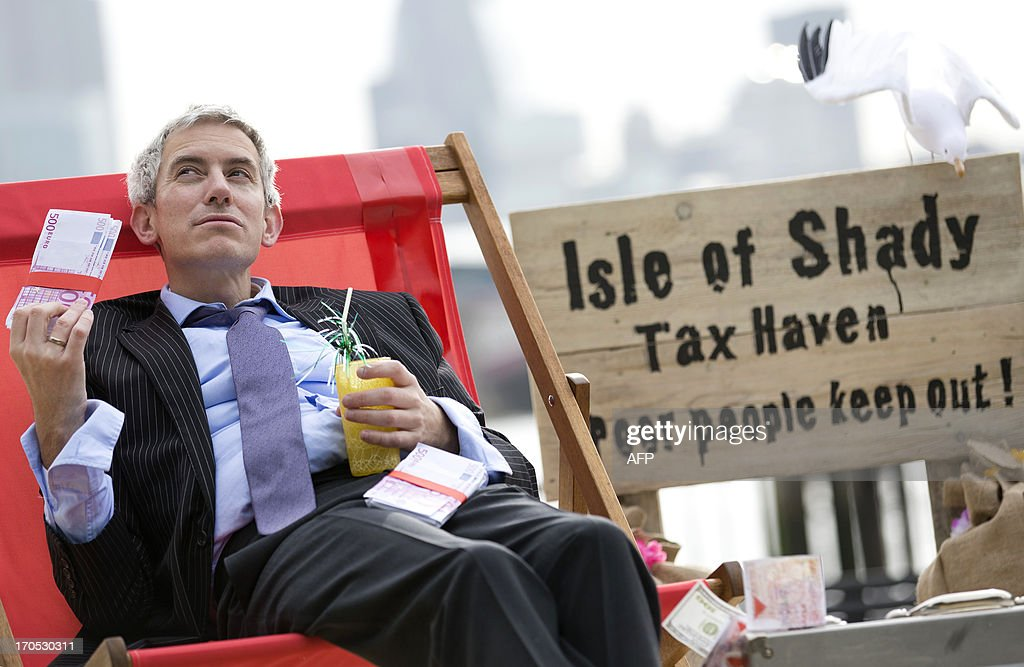 A protestor dressed as a businessman fans himself with a wad of fake 500 Euro notes on a protest site named by participants as the 'Isle of Shady Tax Haven' in London on June 14, 2013, ahead of the G8 summit as campaigners call for a crackdown on tax havens. The G8 Summit will be held in Northern Ireland on June 17 and 18, 2013.