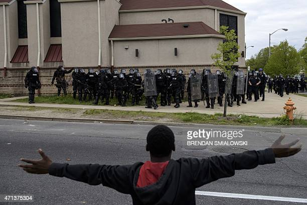 A protestor gestures before riot police on April 27 2015 in Baltimore Maryland on April 27 2015 in Baltimore Maryland Violent street clashes erupted...