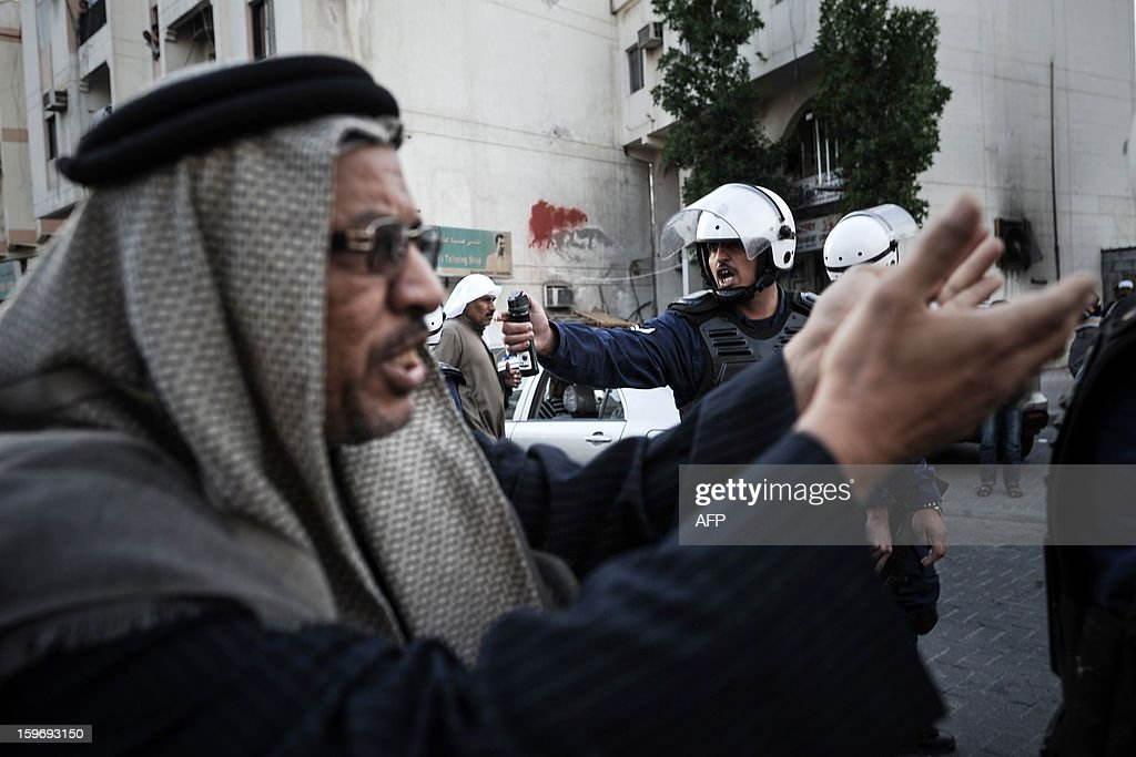 A protestor gestures in front of a riot policeman use a pepper spray during a demonstration called for by the February 14 Youth Coalition, an Internet group that regularly calls for protests in the Shiite-majority kingdom on January 18, 2013 in the capital Manama. Bahrain's government said the demonstration had not been authorised and warned security forces would prevent it from going ahead. AFP PHOTO/MOHAMMED ALSHAIKH