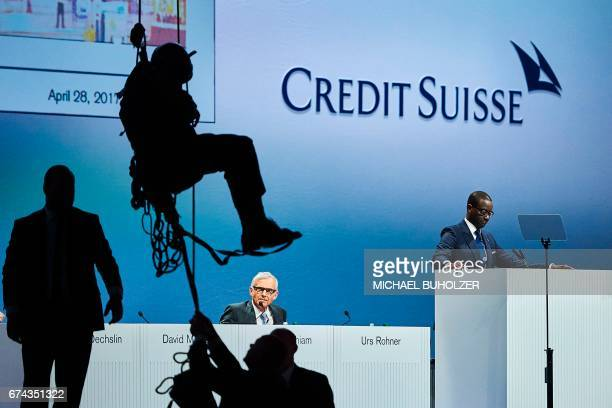 A protestor hanging on ropes after mounting a banner reading 'Credit Suisse Stop dirty pipeline deals' is taken down as Credit Suisse CEO Tidjane...