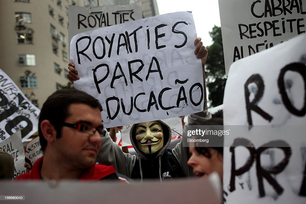 Protestor hold signs during a demonstration in Rio de Janeiro, Brazil, on Monday, Nov. 26, 2012. Tens of thousands of residents in Rio de Janeiro attended a rally today urging Brazilian President Dilma Rousseff to veto an oil royalties law that the state's governor claimed will derail the 2016 Olympics. Photographer: Dado Galdieri/Bloomberg via Getty Images