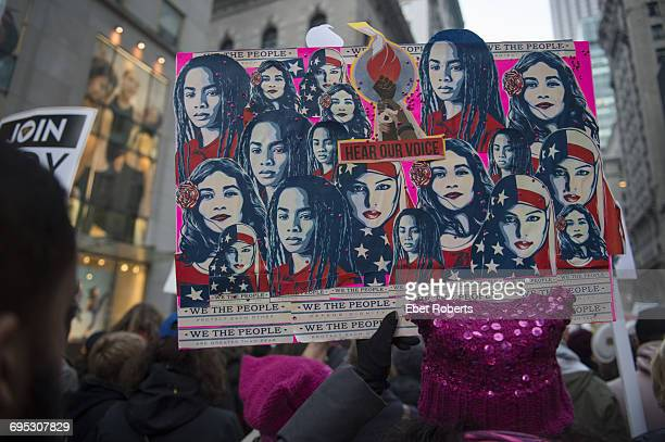 A protestor holding a placard depicting ethnically diverse American women with the words ''hear our voice' at the Women's March in New York City 21st...