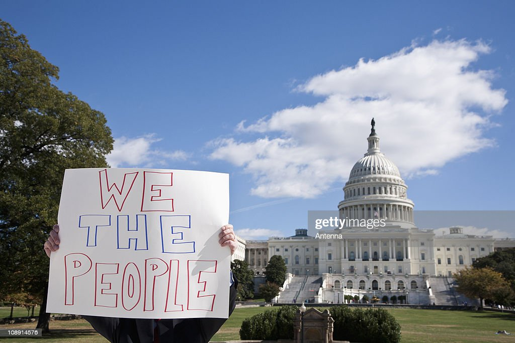 A protestor holding a placard in front of the US Capitol Building : Stock Photo