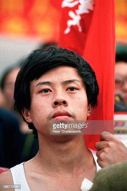A protestor holding a red banner listens to a prodemocracy movement leader speak early one morning in Tiananmen Square Prodemocracy demonstrators and...