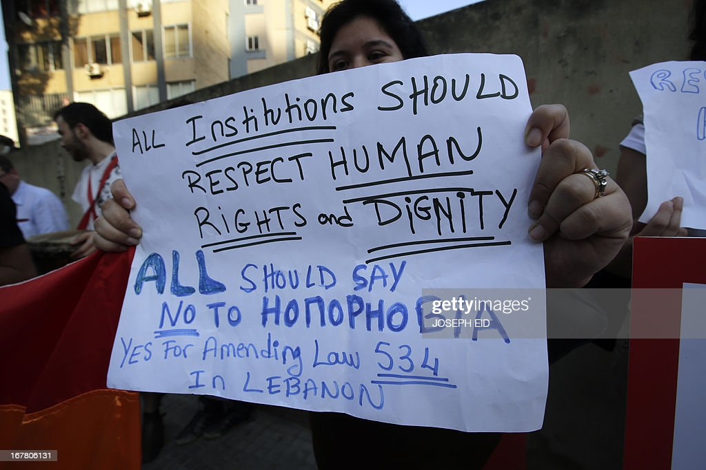 A protestor holds a banner as she attends an anti-homophobia rally in Beirut on April 30, 2013. Lebanese homosexuals, human rights activists and members from the NGO Helem (the Arabic acronym of 'Lebanese Protection for Lesbians, Gays, Bisexuals and Transgenders') rallied to condemn the arrest on the weekend of three gay men and one transgender civilian in the town of Dekwaneh east of Beirut at a nightclub who were allegedly verbally and sexually harassed at the municipality headquarters.