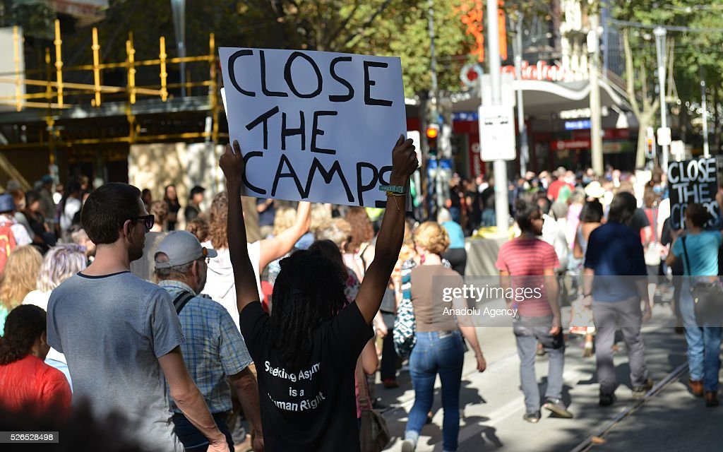 A protestor holds a banner during a protest march demanding that asylum seekers held in off shore detention to be brought to Australia at a rally in Melbourne, Australia on April 30, 2016.